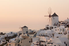 Amazing Sunset over white windmills in  town of Oia and panorama to Santorini island, Thira, Greece Stock Image