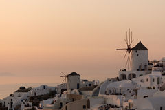 Amazing Sunset over white windmills in  town of Oia and panorama to Santorini island, Thira, Greece Royalty Free Stock Photography