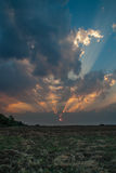Amazing sunset with powerful sunbeams. Inspiring sunset over cultivated land with dramatic sky, clouds and sunbeams stock photos