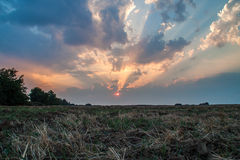 Amazing sunset with powerful sunbeams. Inspiring sunset over cultivated land with dramatic sky, clouds and sunbeams stock photography