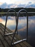 Lakeside Pontoon and Ladders - Finland. Amazing sunset reflections with water lilies and reeds over a lake near Lusi in Finland Stock Images