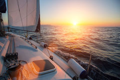 Amazing sunset at sea shot of a luxery yacht boat. Sailing in the wind through the waves Stock Photos