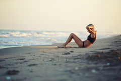 At amazing sunset young girl doing exercises on the beach. At beautiful sunset young athletic girl doing abdominal crunches exercises on the beach stock images
