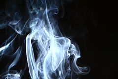 Beautiful abstract contrast blue smoke against the heavy black background. Amazing swirl contrast bright smoke on black background royalty free stock image