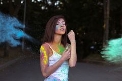 Amazing tanned woman with short hair playing with exploding Holi Stock Photo