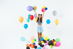 Amazing teen girl looking straight, holding helium ballons on white. Amazing teen girl looking straight, holding fancy helium ballons on white background of Stock Image