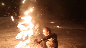 Amazing tribal fire show dance at night on winter under falling snow. Dance group performs with torch lights and. Pyrotechnics stock video