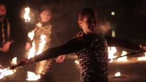 Amazing tribal fire show dance at night on winter under falling snow. Dance group performs with torch lights and. Pyrotechnics stock video footage