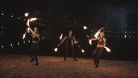 Young fireshow artists juggling staves outdoor stock video