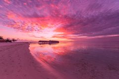Amazing tropical beach sunrise or sunset landscape, luxury water villas and mirror reflection and colorful sky. Sunset or sunrise on tropical beach. Palm trees Royalty Free Stock Photos