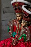 Amazing twins couple with big hat and venetian mask during venice carnival Stock Photo
