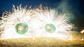Amazing two performers Fire Show with a fireworks. Double O-shape full-round lines with a lot of sparks. And rapt Stock Photo