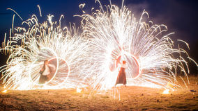 Amazing two performers Fire Show with a fireworks. Double O-shape full-round lines with a lot of sparks. And rapt Royalty Free Stock Photo