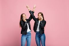 Amazing two young twin sisters with bright smile talk on smartphone with hands up show peace gesture over pink royalty free stock images