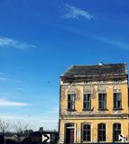 Amazing very old yellow house and perfect blue sky. Old historic building with broken windows Royalty Free Stock Photos