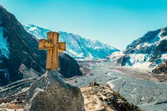 Amazing view alongside Georgian military road, high in the Caucasus mountains. Winter time, high mountain peaks covered with snow. Wooden cross beside the road stock photography
