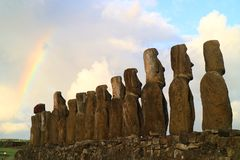 Amazing view of the back of 15 huge Moai statues of Ahu Tongariki with the rainbow on cloudy sky in background. Archaeological site in Easter Island royalty free stock photos