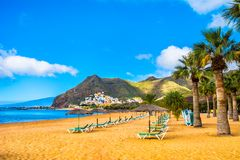 Amazing view of beach las Teresitas with yellow sand, umbrellas,. Longues and palm trees. Location: Santa Cruz de Tenerife, Tenerife, Canary Islands. Artistic Royalty Free Stock Image