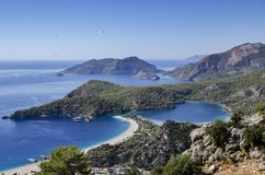 Amazing view of the beach of Oludeniz. From the top we see a beach horseshoe and a blue lagoon. In the sky fly deltoplaneristy Stock Photo