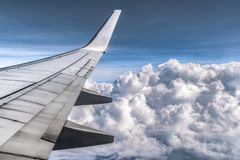 Dramatic clouds from window of Airplane. Wings and all components are visible. Clouds fluffy as cotton balls royalty free stock image