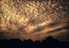 An amazing view of glowing clouds in the sunset sky. An amazing and beautiful view of glowing clouds in the sunset sky.Clouds look like small crystals in the sky stock photo