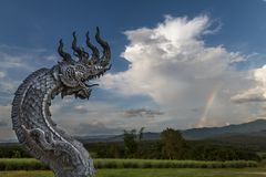 Amazing view with a great traditional thai naga dragon sculpture breathing huge white clouds as fire and smoke stock photography
