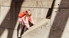 Amazing  view of happy, joyful smiled little girl hiking on concrete wall Royalty Free Stock Photos