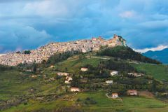 Amazing view of historical city Enna, in cental Sicily, Italy photographed with dark storm clouds and adjacent green landscape. Cityscape, city on a hill stock image