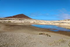 Amazing view of Montana Roja volcano with pond in natural reserve of sand desert in El Medano, Tenerife, Spain.  royalty free stock photos