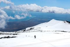 Amazing view from Mount Etna photographed with hikers going down on the snow and sea coast in the background. Magnificent clouds. Close to the top of the royalty free stock photography