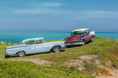 Amazing view of old vintage classic retro cars. Amazing view of old vintage classic cars, parked together on the cliff against tranquil azure ocean and blue sky Royalty Free Stock Images
