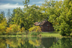 Amazing view of an old vintage wooden abandoned cabin, standing in woods reflected in lake calm water on sunny warm autumn day. Charming gorgeous view of old royalty free stock image