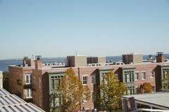 Amazing view from a rooftop of a hip trendy apartment building overlooking the water in the bay. With trees, brick, and cool architecture stock images