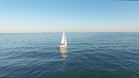 Amazing view of sail yachts sailing in open sea. Blue sea with sun reflections. Drone view - birds eye angle. Amazing view of sail yachts sailing in open sea at stock video