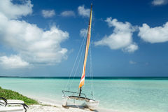 Amazing view of sailboat resting on white sand Cuban beach on background of bright tranquil turquoise ocean water and deep blue sk Royalty Free Stock Images