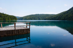 Amazing view of the small old wooden pier and landscape of forest and lake surrounded by mountains in national park plitvice lakes Royalty Free Stock Image