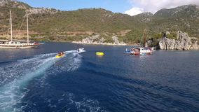 Amazing view to yachts sailing in open sea at sunny day with people swimming and doing watersports