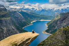 Amazing view with Trolltunga and a girl sitting on it. Norway Royalty Free Stock Photos