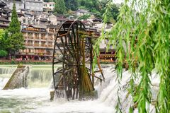 Amazing view of water wheel and waterfall, Phoenix Ancient Town. Fenghuang, China - September 22, 2017: Amazing view of water wheel and scenic waterfall on the royalty free stock photo