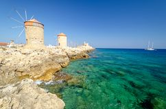 Amazing view on windmill and azure sea in Rhodes town, Greece. Mandraki harbour in Rhodes town in Greece royalty free stock images
