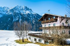 Amazing view of winter wonderland mountain scenery with traditional mountain chalet in the Alps on a sunny day with blue sky.  royalty free stock images