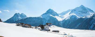 Amazing view of winter wonderland mountain scenery with traditional mountain chalet in the Alps on a sunny day with blue sky.  royalty free stock image