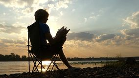 Young Man Sits, Thinks, Reads Something in His Notepad, on a Riverbank in Slo-Mo. An Amazing View of a Young Man Who Sits in a Folding Chair on the Dnipro stock video footage