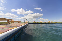 Amazing views over the pool area with wooden sun loungers. Royalty Free Stock Photo