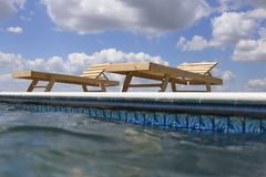 Amazing views over the pool area with wooden sun loungers. Royalty Free Stock Photography