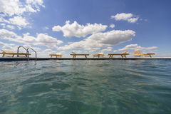 Amazing views over the pool area with wooden sun loungers. Royalty Free Stock Images