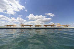 Amazing views over the pool area with wooden sun loungers. Stock Images