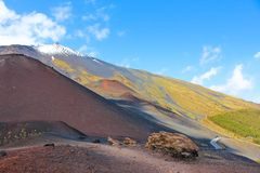 Amazing volcanic landscape on Mount Etna, Sicily, Italy taken from adjacent Silvestri craters on a sunny day. Snow on the very top. Of the mountain. European royalty free stock images