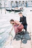 Amazing walk in Venice. Young pretty girl in pink dress put her hand in water in venetian canal, young man in black hugging the gi stock photos