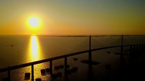 Amazing warm pink orange evening sunset over huge highway road steel bridge across sea in 4k aerial drone seascape view stock footage